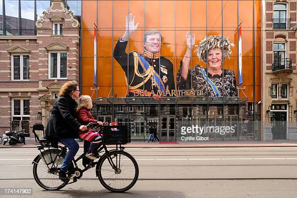 Woman and a baby on a bicycle ride past portraits of Queen Beatrix of the Netherlands and her son, Willem-Alexander, displayed in front of a theater...