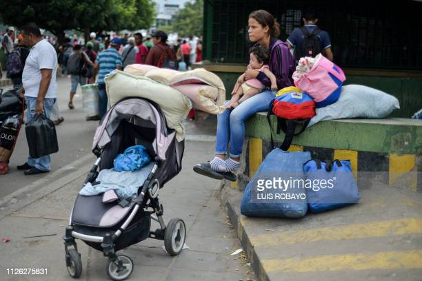 A woman and a baby wait in Cucuta Colombia after crossing the Simon Bolivar International bridge from San Antonio de Tachira in Venezuela on February...