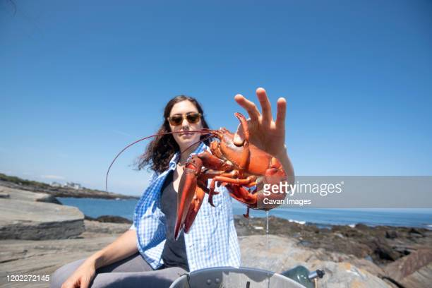 a woman and a boiled lobster - portland maine stock pictures, royalty-free photos & images
