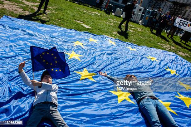 A woman and a boy are seen lying on a big flag of the EU during the protest A day before the anniversary of the founding Treaty of the European Union...