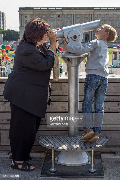 A woman and a boy look through a telescope towards a giant map of Berlin in 1775th scale complete with giant coloured pins marking sites of...