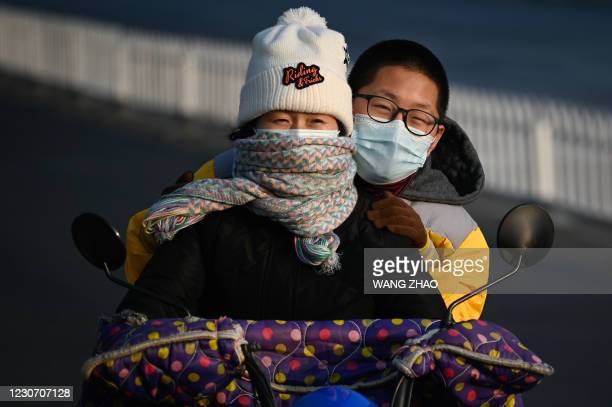 Woman and a boy ride an electric bicycle along a street in Beijing on January 21, 2021.
