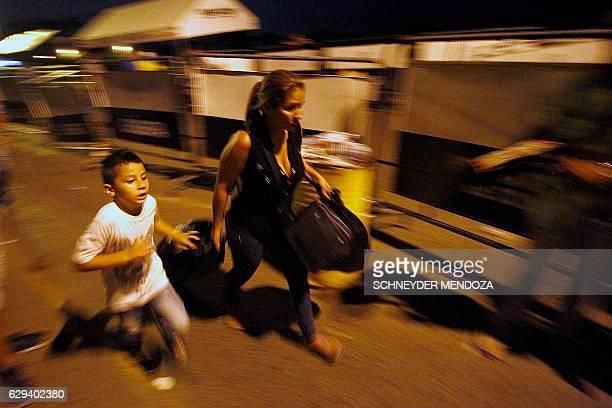 TOPSHOT A woman and a boy run across the Simon Bolivar bridge on the Colombian border with Venezuela on December 12 2016 Venezuelan President Nicolas...