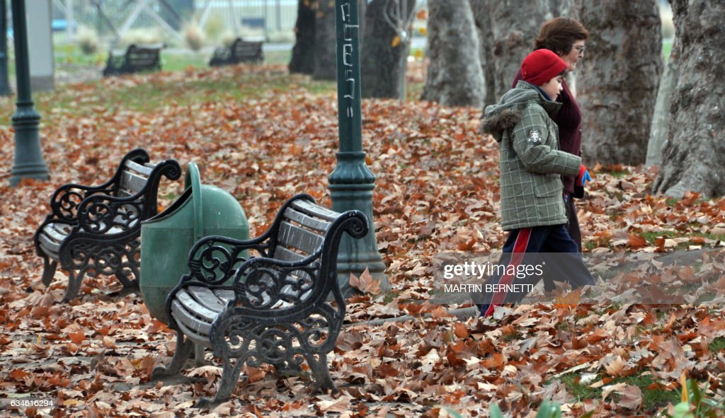 A woman and a boy walk during a cold fall morning in a park of Santiago, Chile, on June 16, 2009. AFP PHOTO/Martin BERNETTI /