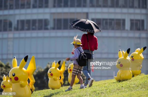 A woman and a boy walk past statues of Pikachu a character from Pokemon series game titles during the Pikachu Outbreak event hosted by The Pokemon Co...