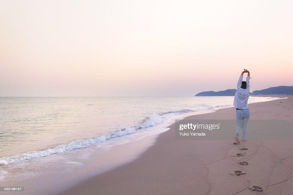Woman and a Calm Beach in Dawn : Stock Photo