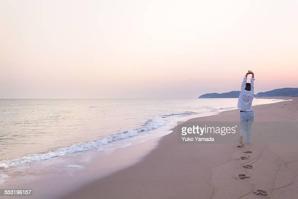 Woman and a Calm Beach in Dawn