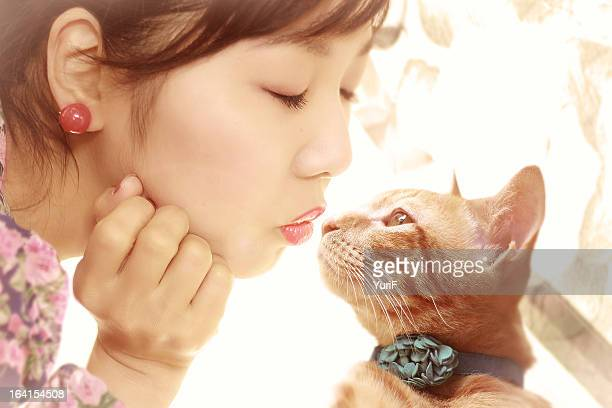 Woman and a cat kissing.