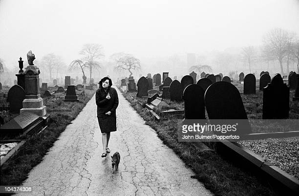 A woman and a cat walk through a cemetery in Wakefield West Yorkshire circa 1963
