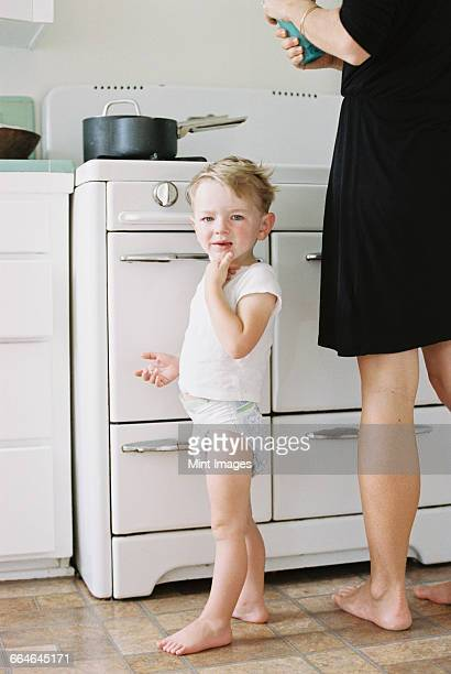 a woman and a child, a young boy standing barefoot in a kitchen. - diaper boy stock photos and pictures