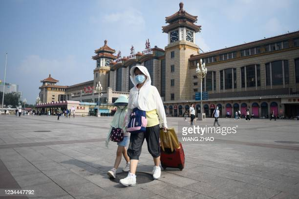 Woman and a child arrive at Beijing railway station on August 4, 2021.