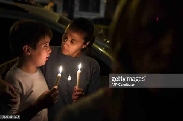 A woman and a child hold candles during a vigil organised in front of the Politecnico high school where five Argentine citizens killed on October 31...