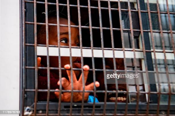 Woman and a child is seen in a police van as South African Police assisted by Cape Town Metro Police forcefully removed refugees from various...
