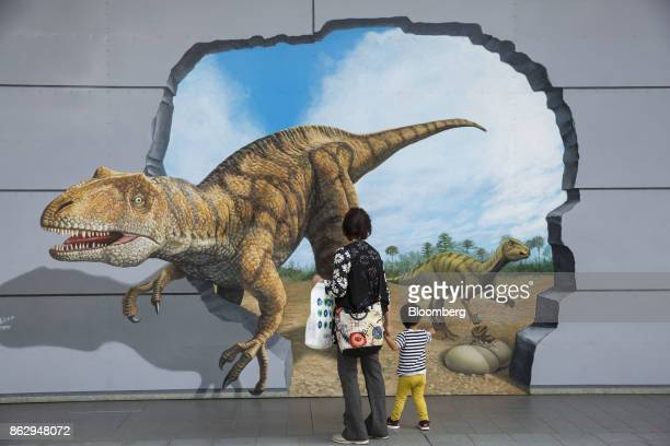 A woman and a child look at a mural of dinosaurs outside Fukui station in Fukui Japan on Wednesday Oct 11 2017 Fukui Prefecture has one of the lowest...