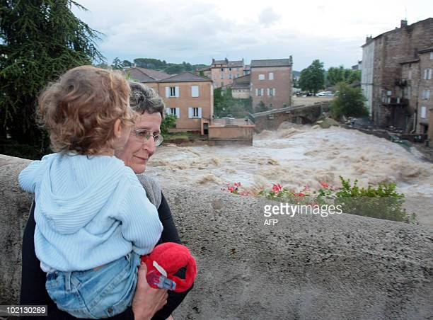 A woman and a child looks at Nartuby river in flood in the aftermath of flooding in a western district of the French south eastern city of...