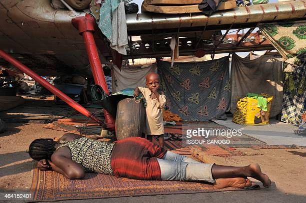 Woman and a child rest under a plane in the camp for displaced persons at the Mpoko airport in Bangui, on January 21 a day after the election of...
