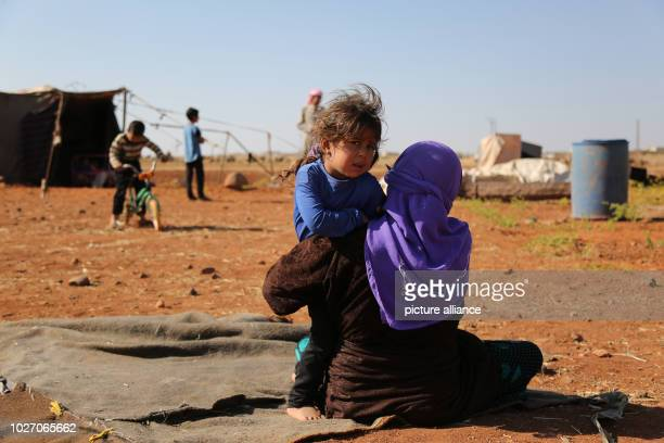 A woman and a child sit on the ground in front of their tent at a camp built by displaced people near a Turkish observation point after they were...