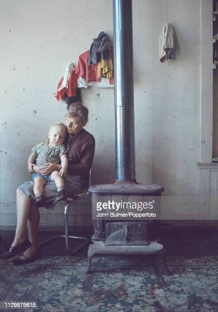 A woman and a child sitting near an old coal stove Pike County Kentucky US 1967
