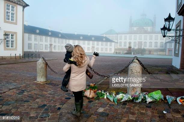 A woman and a child stand in front of a makeshift memorial of flowers placed in front of Fredensborg Palace in Fredensborg Denmark on February 14...