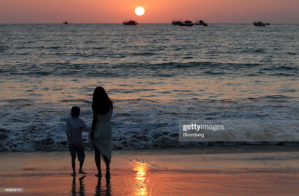 A woman and a child stand on a beach as the sun sets behind fishing boats in Jimbaran, Bali, Indonesia, on Saturday, Oct. 5, 2013. Indonesia's central bank kept its key interest rate unchanged after its most aggressive tightening cycle in almost eight years as inflation pressure eased. Photographer: SeongJoon Cho/Bloomberg via Getty Images