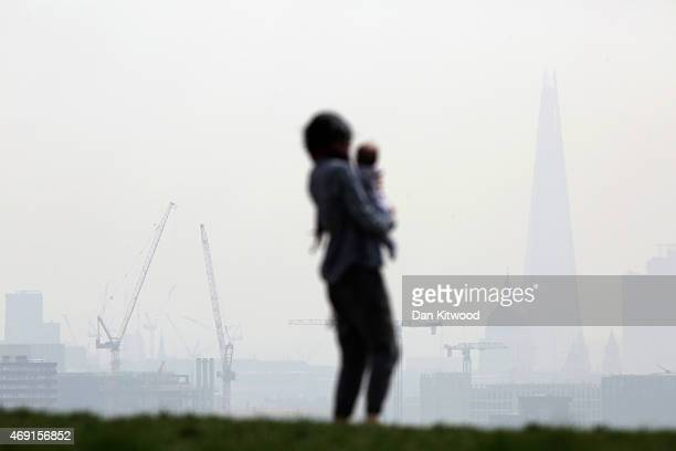 A woman and a child stand on Parliament Hill in Hampstead Heath overlooking an overcast Central London on April 10 2015 in London England Air...