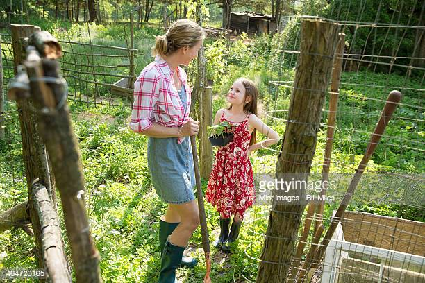 A woman and a child standing at the open gate of a fenced enclosure. A girl holding a small plant in a pot.