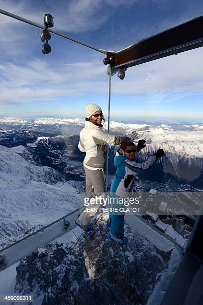 A woman and a child visit the 'Step into the Void' glass skywalk overlooking the French Alps on top of a 3842metre peak in Chamonix on December 23...