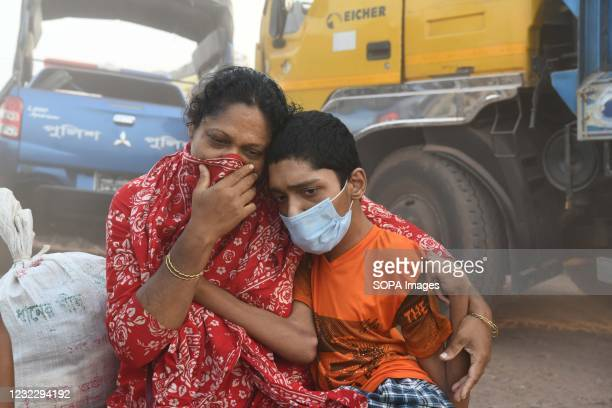 Woman and a child wait for means to return home before lockdown at Mawa Ferry terminal near Dhaka. Bangladesh extends nationwide lockdown measures...