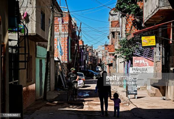 Woman and a child walk as a man rides a bycicle along a street at the Villa 21-24 shantytown in Buenos Aires on September 29 amid the new coronavirus...