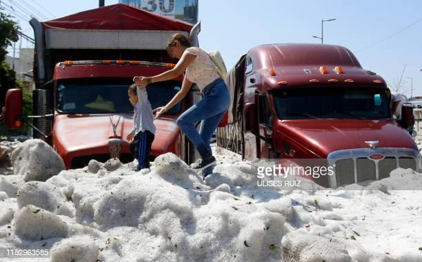 Woman and a child walk on hail in the eastern area of Guadalajara, Jalisco state, Mexico, on June 30, 2019. - The accumulation of hail in the streets...