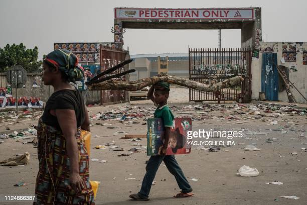 A woman and a child walk past shoes and items lying on the ground on February 13 2019 in front of the main entrance of the Adokiye Amiesimaka Stadium...