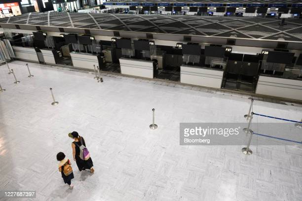 Woman and a child walk through a near-empty departures hall of Narita Airport in Narita, Chiba Prefecture, Japan, on Sunday, July 19, 2020. More...