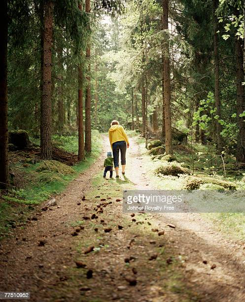 A woman and a child walking in the forest Linkoping Sweden.
