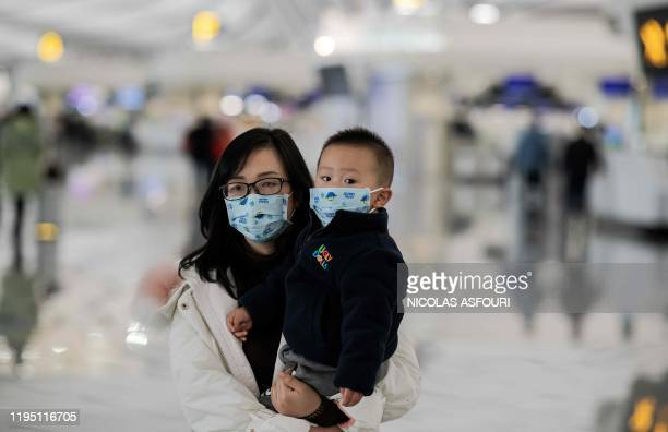 TOPSHOT A woman and a child wearing protective masks walk toward checkin counters at Daxing international airport in Beijing on January 21 2020 The...