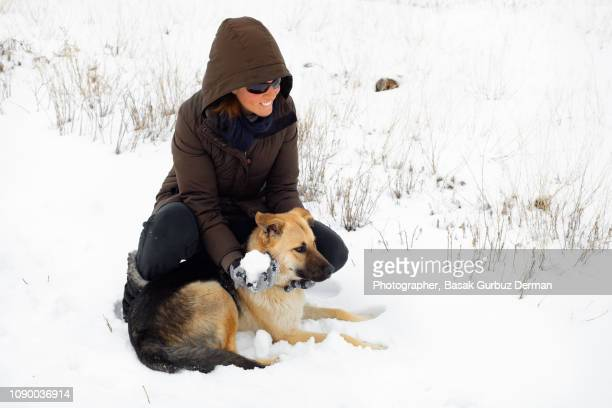 A woman and a dog hugging and leaning each other. They are playing with snowball in winter.