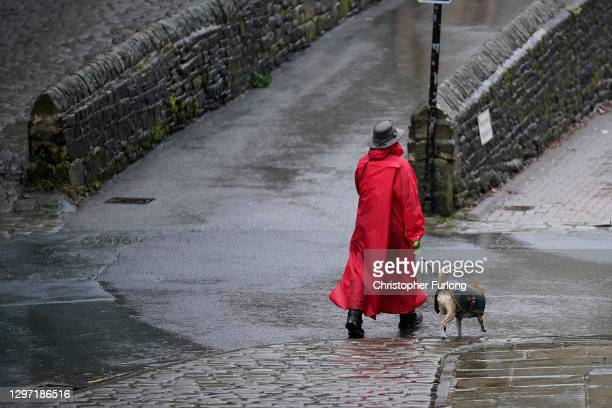 Woman and a dog walk in the rain in Hebden Bridge as local shops and businesses install their flood defences on January 19, 2021 in Hebden Bridge,...