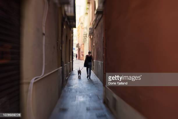 Woman and a dog walking in a very narrow alley