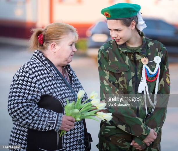Woman and a female soldier before a wreath-laying ceremony in the district of Liski, Shchuchye. Wreath-laying ceremony of a German wreath in honour...