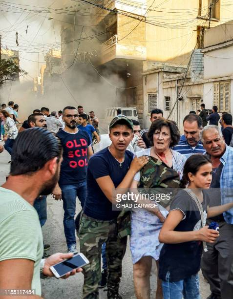 Woman and a girl are escorted away from the scene of a car bomb explosion outside the Syriac Orthodox Church of the Virgin Mary in the predominantly...