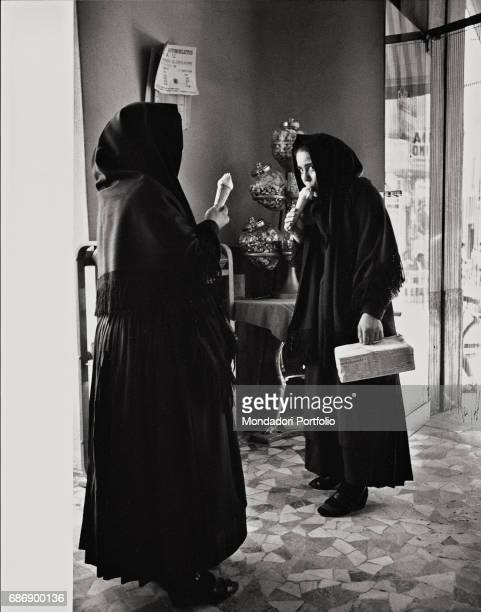A woman and a girl eating ice cream in an ice cream parlour in Oristano This picture is taken from the monography Mario De Biasi Il mio sogno Š qui...