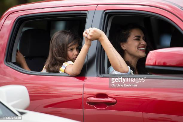 Woman and a girl hold hands while singing during an Easter drive-in service at Glasgow Farm in Virginia due to the coronavirus outbreak on Sunday,...