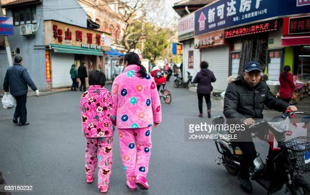 A woman and a girl in pink pyjamas walk down a street in Shanghai on January 31 2017 / AFP PHOTO / Johannes EISELE