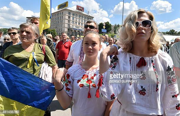 A woman and a girl make the sign of the cross as people take part in a rally by Maidan activists at Independence Square in Kiev calling upon the...