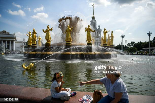 A woman and a girl rest by the famous Druzhba Narodov fountain in the AllRussia Exhibition Centre a trade show and amusement park with temperatures...