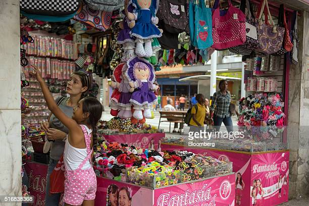 A woman and a girl shop at the Fantasia Virtual store in Medellin Colombia on Monday March 14 2016 Colombia's central bank raised its benchmark...