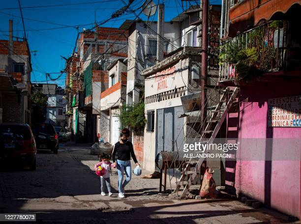 Woman and a girl walk along an alley at the Padre Carlos Mugica neighborhood, also known as Villa 31 shantytown, in Buenos Aires, on July 25 amid a...