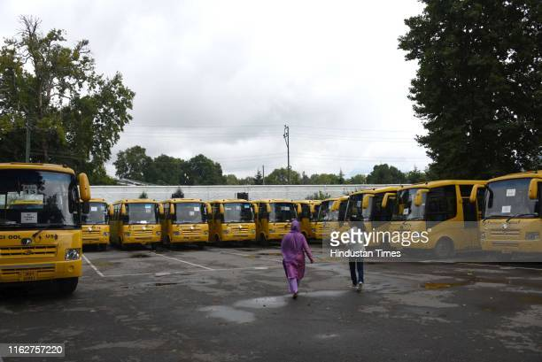 A woman and a girl walk by parked school buses in a school complex on August 19 2019 in Srinagar India Teachers reported to work in many schools in...