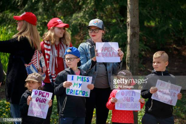 Woman and a group of children, hold placards during the demonstration. Protesters gather outside Indiana Governor Eric Holcomb's mansion in the 4700...