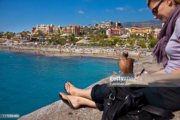 Woman and a hairy man sitting on a rock next to the beach Playa del Duque in Playa de las Americas on March 25 2011 in Tenerife Spain Tenerife is the...