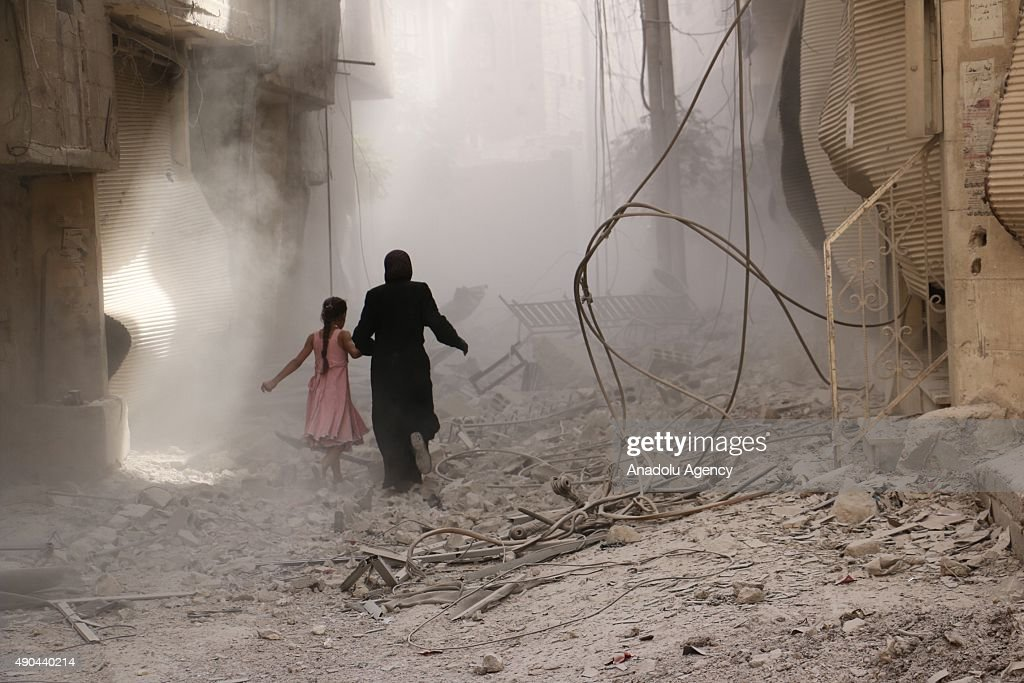 A woman and a kid run through the smoke after an air-strike staged by Syrian regime forces to the opposition residential areas in Duma district in the Eastern Ghouta area of Damascus, Syria on September 28, 2015.